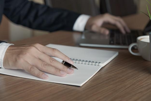 Bedrijfsmensenhand die bij een computer werken en aan een blocnote met een pen in het bureau schrijven Premium Foto