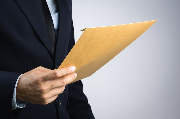 Bedrijfsmensenhand die een zelfdichtend bruin envelopdocument houden Premium Foto