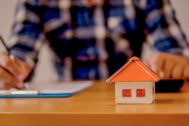 Bedrijfsonroerende goederenconcept, huismodel op houten en vage achtergrond. Premium Foto