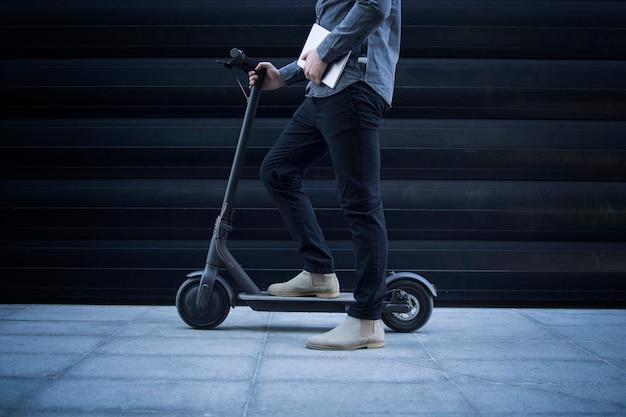 Bedrijfspersoon met tabletcomputer op zijn elektrische scooter woon-werkverkeer voertuig Gratis Foto