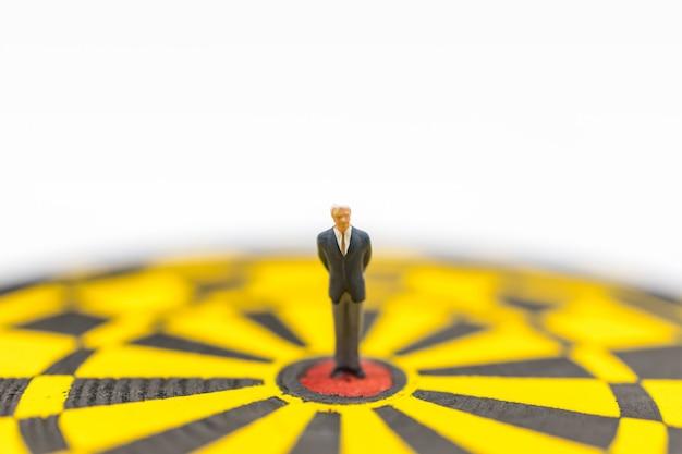 Bedrijfsplanning, doel en doel dekking concept. mensen van het zakenman de miniatuurcijfer die zich op rood puntcentrum bevinden van geel zwart dartboard Premium Foto