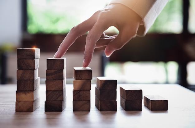Bedrijfsplanning en groeiconcepten, een zakenman gebruikt zijn vinger om de houten blokken op te klimmen Premium Foto