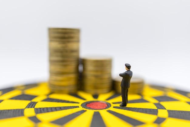 Bedrijfsplanning, geld, doel en doel dekking concept. mensen van het zakenman de miniatuurcijfer die en zich aan gouden muntstukken op geel en zwart dartboard bevinden kijken te kijken. Premium Foto