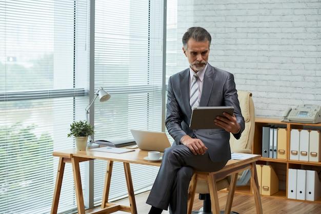Bedrijfsprofessional die met digitale tablet in zijn milieuvriendelijk bureau gezet aan het houten bureau werken Gratis Foto