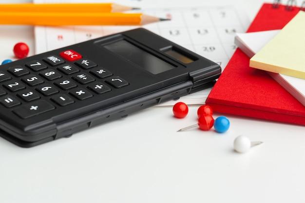 Bedrijfsstilleven met calculator op lijst in bureau. Premium Foto