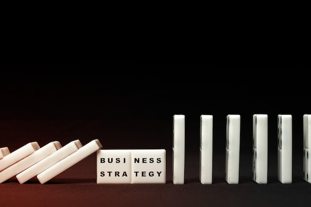Bedrijfsstrategie geïllustreerd op domino-effect Premium Foto