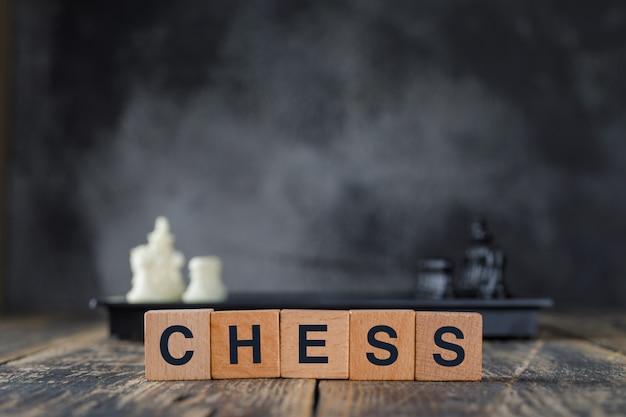 Bedrijfsstrategieconcept met cijfers aangaande schaakbord, houten kubussen op mistig en houten lijst zijaanzicht. Gratis Foto