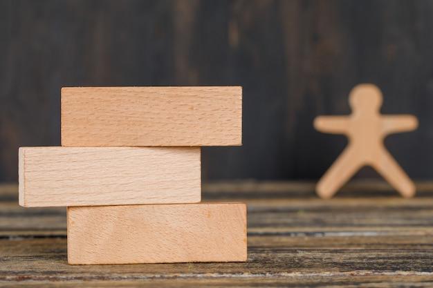 Bedrijfsstrategieconcept met houten blokken, menselijk cijfer aangaande houten lijst zijaanzicht. Gratis Foto