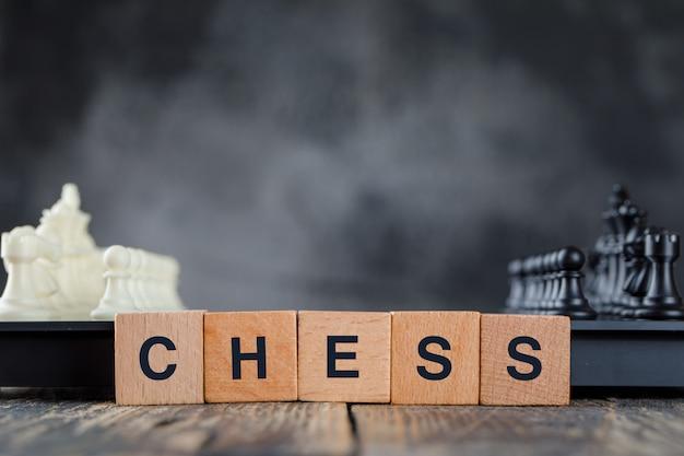 Bedrijfsstrategieconcept met schaakbord en cijfers, houten kubussen op mistig en houten lijst zijaanzicht. Gratis Foto