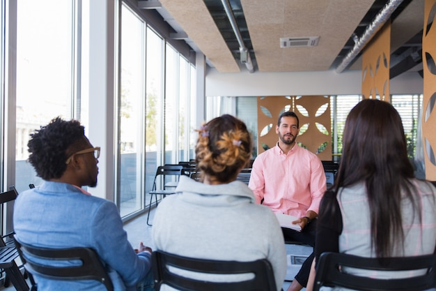 Bedrijfstrainer die ervaring met groep collega's deelt Gratis Foto