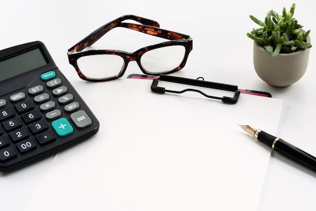 Bedrijfsvoorwerpen, klembord met leeg blad van document, pen, glazen en calculator Premium Foto