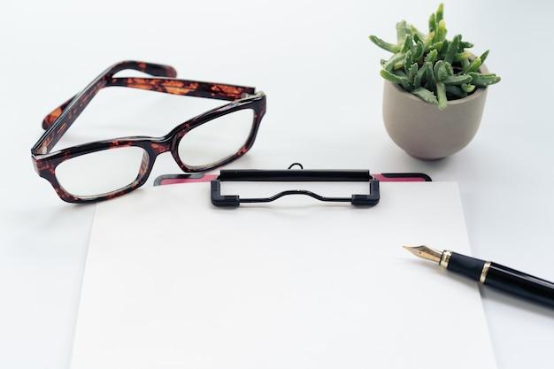Bedrijfsvoorwerpen, klembord met leeg blad van document, pen, glazen op witte achtergrond Premium Foto