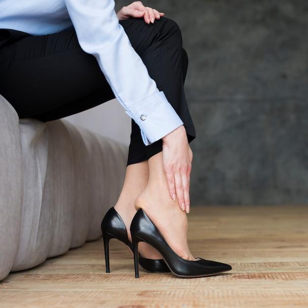 Bedrijfsvrouw die aan benenspanning lijden Gratis Foto