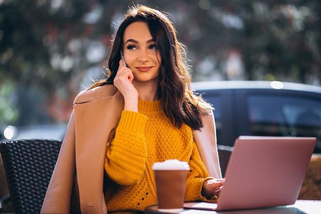 Bedrijfsvrouw die aan een een computer en het drinken koffie werken Gratis Foto