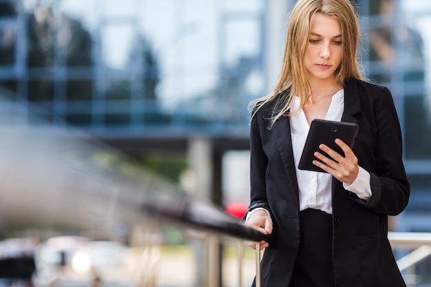 Bedrijfsvrouw die een tablet in openlucht gebruiken Gratis Foto