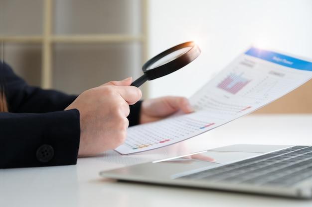 Bedrijfsvrouw die het overdrijven gebruiken om jaarlijkse balans te herzien. audit en controleer integriteit vóór investeringsconcept. Premium Foto
