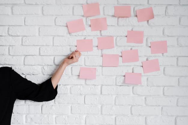 Bedrijfsvrouw die kleverige nota's over muur plakken Gratis Foto
