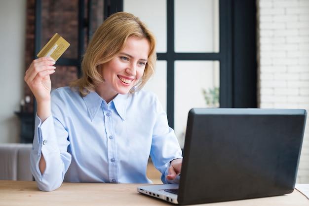 Bedrijfsvrouw die laptop en creditcard gebruiken Gratis Foto