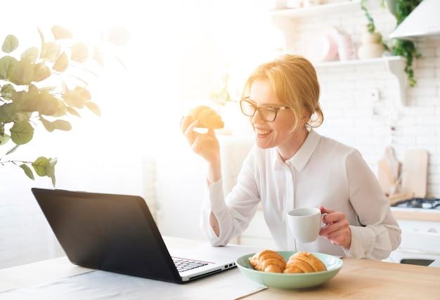 Bedrijfsvrouw die laptop met behulp van terwijl het eten van croissant Gratis Foto