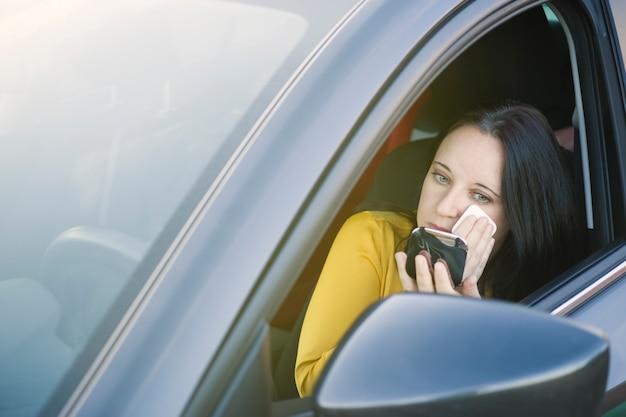Bedrijfsvrouw die met blauwe ogen op make-up in de auto zetten terwijl in een opstopping Premium Foto