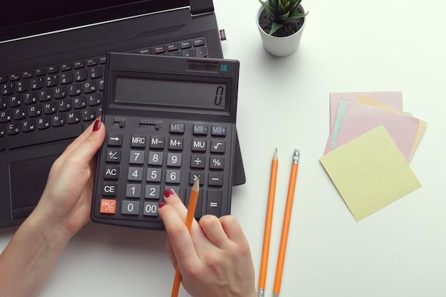 Bedrijfsvrouw die met financiële gegevenshand werken die calculator gebruiken Premium Foto