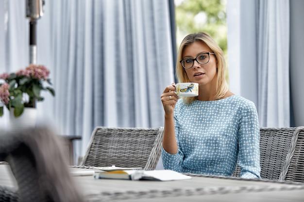 Bedrijfsvrouw die met koffie bij een lijst aangaande het de zomerterras glimlachen. Premium Foto