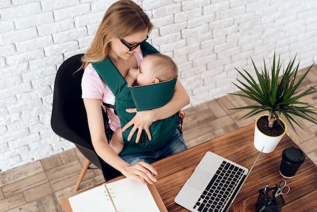 Bedrijfsvrouw die met pasgeboren in babyslinger werken Premium Foto
