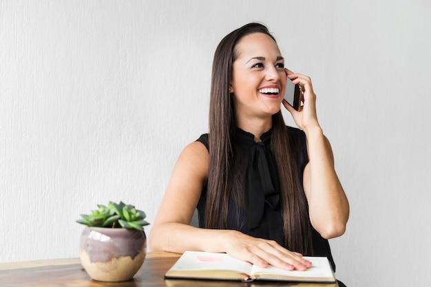 Bedrijfsvrouw die op de telefoon lachen Gratis Foto