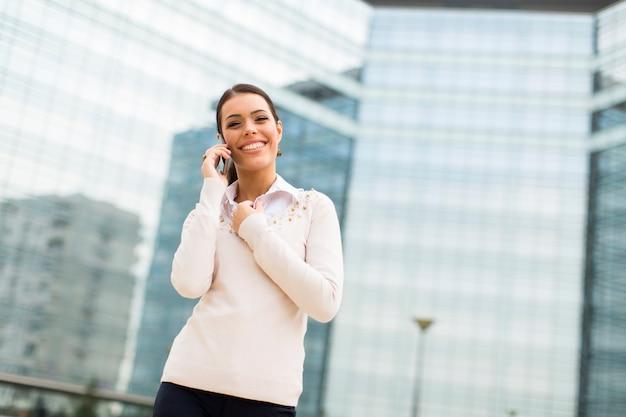 Bedrijfsvrouw die op mobiele telefoon voor bureau spreken Premium Foto