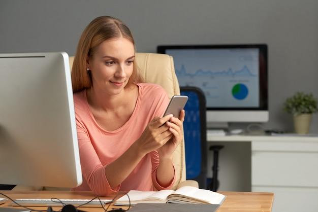 Bedrijfsvrouw die privé berichten texting op haar werkplaats Gratis Foto