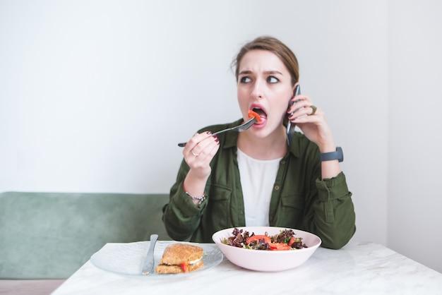 Bedrijfsvrouw die salade eten en op telefoon in restaurant op achtergrond van lichte muur spreken. Premium Foto