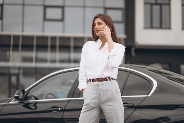 Bedrijfsvrouw die zich door de auto bevinden en telefoon met behulp van Gratis Foto