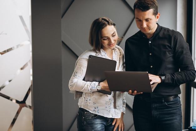 Bedrijfsvrouw en bedrijfsman collega's die aan laptop werken Gratis Foto