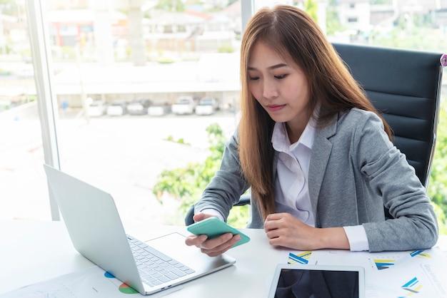Bedrijfsvrouw gebruiken mobiel met laptop op bureau in bureau. Premium Foto