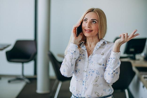 Bedrijfsvrouw in bureau die telefoon met behulp van Gratis Foto
