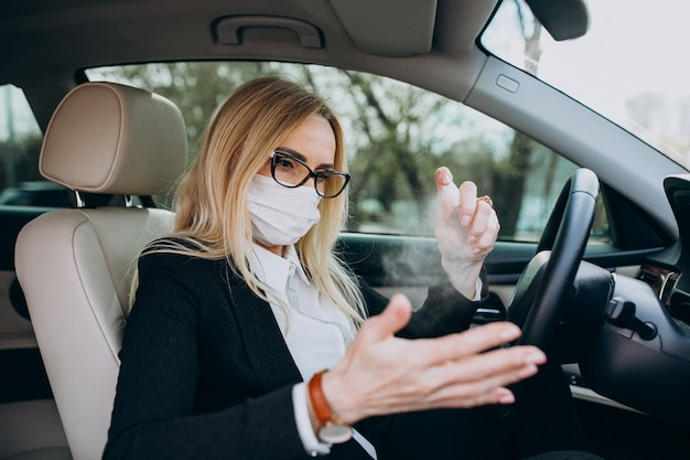 Bedrijfsvrouw in de zitting van het beschermingsmasker in een auto die antiseptisch gebruiken Gratis Foto