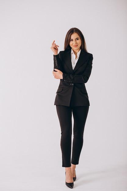 Bedrijfsvrouw in zwart kostuum dat op witte achtergrond wordt geïsoleerd Gratis Foto
