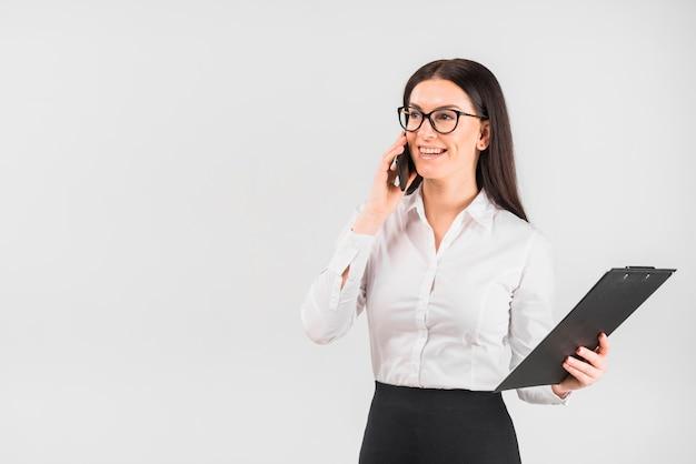 Bedrijfsvrouw met klembord die telefonisch spreken Gratis Foto