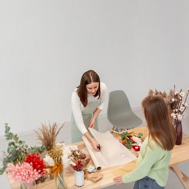 Bedrijfsvrouwen die bij bloemwinkel werken met plannen Gratis Foto
