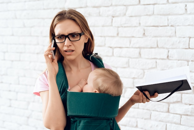 Bedrijfsvrouwen sprekende telefoon en pasgeboren houden. Premium Foto