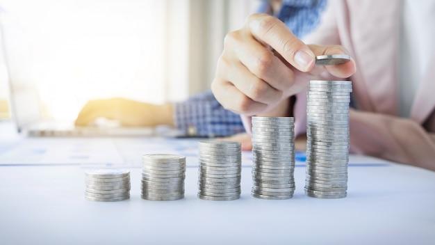 Bedrijfsvrouwen zetten muntstukken geld voor geldgroei concept, geld besparen voor de toekomst. Premium Foto