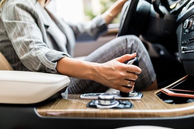 Bedrijfsvrouwenhand die een auto automatisch toestel met behulp van. vrouw rijden concept Gratis Foto