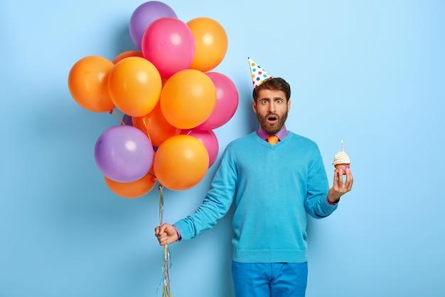 Bedwelmde man met verjaardagshoed en ballonnen poseren in blauwe trui Gratis Foto
