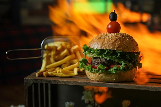 Beef hamburger sla tomaat komkommer olijven frietjes zijaanzicht Gratis Foto