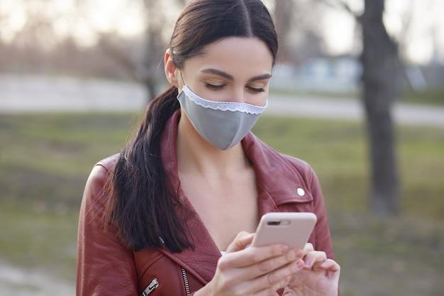 Beeld dat van aanbiddelijk meisje met prettige verschijning, zich openlucht met slimme telefoon in handen, het nieuws van de damelezing over het verspreiden van gevaarlijk coronavirus bevindt Premium Foto