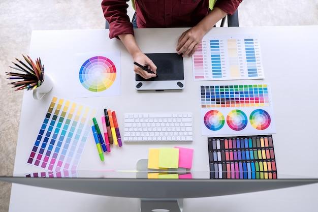 Beeld van creatieve grafische ontwerper die aan kleurselectie werken en op grafiektablet trekken Premium Foto