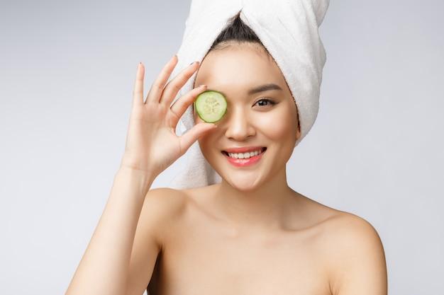 Beeld van de de huidzorg van schoonheids het jonge aziatische vrouwen met komkommer op witte studio als achtergrond. Premium Foto