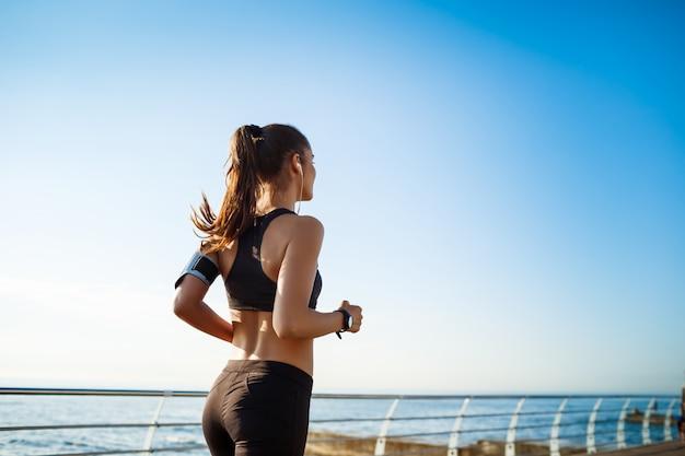 Beeld van de jonge aantrekkelijke jogging van de geschiktheidsvrouw met overzees op muur Gratis Foto