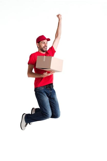 Beeld van een jonge leveringsmens die en doos springt houdt Gratis Foto