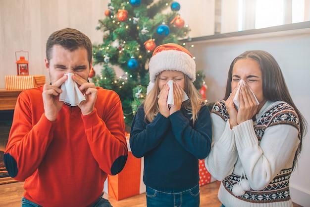 Beeld van familie die aan ziekte lijdt. ze snuiten hun neus met servetten. Premium Foto